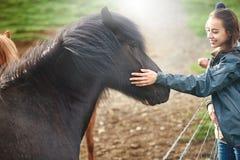 抚摸马的妇女 免版税库存照片