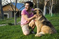 抚摸他的蓬松狗的英俊的亚裔人在一个晴天在庭院里 免版税库存照片