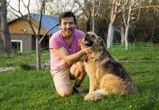 抚摸他的蓬松狗的英俊的亚裔人在一个晴天在庭院里 免版税图库摄影