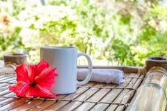 抢劫与在竹桌,在平均观测距离的咖啡杯上的cappuchino 免版税图库摄影