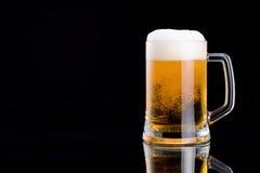 抢劫与泡沫盖帽的新鲜的啤酒在黑色的 库存图片