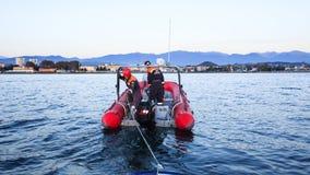 抢救拖曳从海的海洋服务一条残破的小船 图库摄影