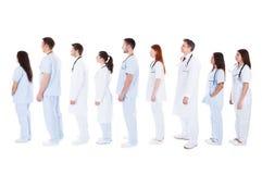 医护人员站立在队列的大小组 库存图片