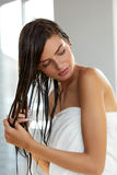 护发 有湿头发的美丽的妇女在巴恩以后的毛巾 库存图片