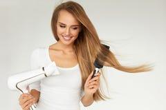 护发 烘干美丽的长的头发的妇女使用烘干机 免版税库存照片