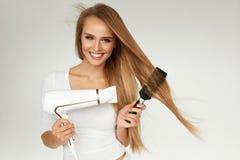 护发 烘干美丽的长的头发的妇女使用烘干机 免版税库存图片