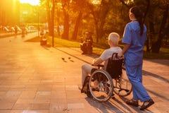 护士和在观看美好的日落的轮椅坐在公园的老人 免版税库存照片