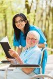 护士和患者读书 免版税库存图片