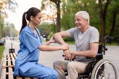 护士在公园认真地检查一名年长患者的手肘一条长凳的 免版税库存图片