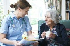 护士在家谈论医疗笔记与资深妇女 免版税库存图片