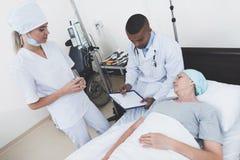 护士在患者旁边站立 医生在有癌症的一名妇女旁边坐 免版税库存照片
