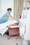 护士在男性患者的安装透析 免版税库存照片