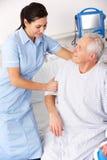 护士帮助的男性患者在英国A&E 免版税库存照片