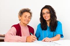 护士帮助的老人登记老人院 免版税库存图片