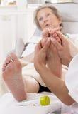 护士或对待一名资深妇女的脚的看护者 免版税库存图片