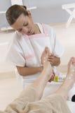 护士或按摩一名年长妇女的脚的看护者 库存图片