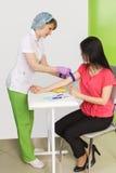 护士投入止血带给血液的汇集的患者从一条静脉的分析的 图库摄影