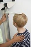 护士测量的男孩的高度 免版税库存图片