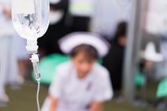 护士照顾是接受盐在的患者 免版税库存照片