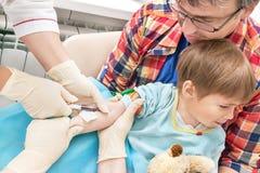 护士的手从从孩子的一条静脉收集血液 库存图片