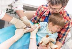 护士的手从从孩子的一条静脉收集血液 库存照片