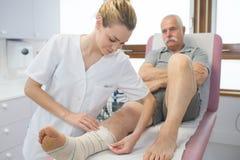 护士藤条在腿患者熔铸了在医院 免版税库存图片