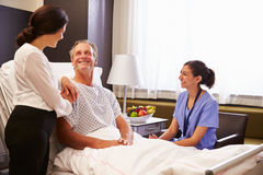 护士谈话与男性患者和妻子在医院病床上 库存照片