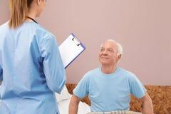护士谈话与老人 医疗协助 免版税库存照片