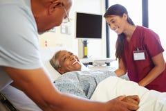 护士谈话与资深夫妇在医房 免版税库存照片