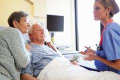 护士谈话与资深夫妇在医房 库存照片