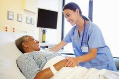 护士谈话与资深妇女在医房 图库摄影