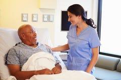 护士谈话与资深男性患者在医房 库存图片