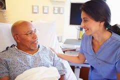 护士谈话与资深男性患者在医房 库存照片