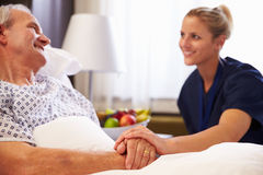 护士谈话与资深男性患者在医院病床上 免版税库存照片