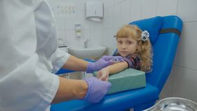 护士采取从一条静脉的血样在小女孩的胳膊 库存图片