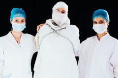 护士镇静下来的拘身衣人 图库摄影