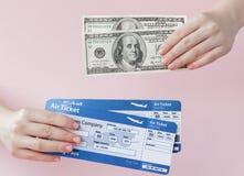 护照、美元和机票在妇女手上在桃红色背景 r 免版税库存图片