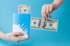 护照、美元和机票在妇女手上在蓝色背景 r 免版税库存图片