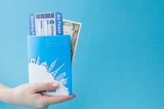 护照、美元和机票在妇女手上在蓝色背景 r 库存图片