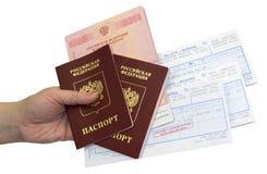 护照和票在一只手上在背景 免版税库存照片