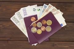 护照和金钱在木桌上 合法的欧洲钞票、捷克语硬币和的钞票 金钱的非法迁移 图库摄影