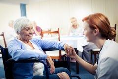 护理互动与轮椅的一名资深妇女 免版税库存图片
