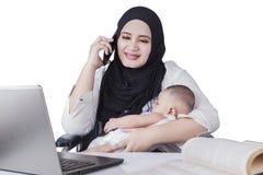 护理她的婴孩的繁忙的母亲 免版税库存照片