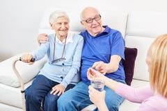 护理的妇女给一种片剂前辈 免版税库存图片