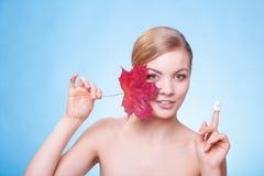 护肤。少妇女孩的面孔有红槭叶子的。 免版税图库摄影
