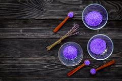 护肤和放松的化妆用品 在黑暗的木背景顶视图拷贝空间的淡紫色紫罗兰色温泉盐 库存照片