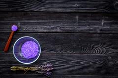 护肤和放松的化妆用品 在darlk木背景顶视图拷贝空间的淡紫色紫罗兰色温泉盐 免版税库存图片