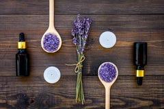 护肤和放松 化妆用品和芳香疗法概念 淡紫色温泉盐和油在黑暗的木背景顶视图 免版税库存图片