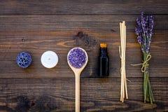 护肤和放松 化妆用品和芳香疗法概念 淡紫色温泉盐和油在黑暗的木背景顶视图 免版税图库摄影