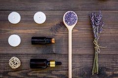 护肤和放松 化妆用品和芳香疗法概念 淡紫色温泉盐和油在黑暗的木背景顶视图 图库摄影